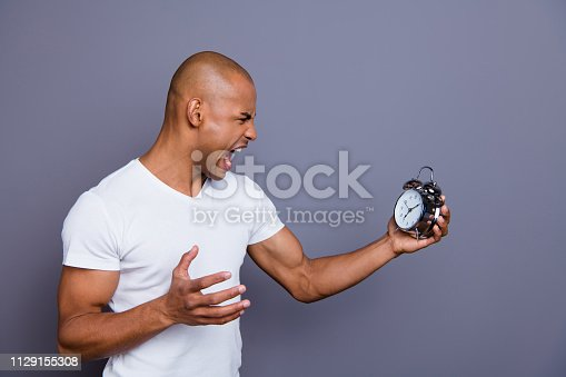 istock Close up side profile photo sick mad unhealthy dark skin he him his macho bald head puzzled hold clock hopelessness despair yell loudly wearing white t-shirt outfit clothes isolated grey background 1129155308