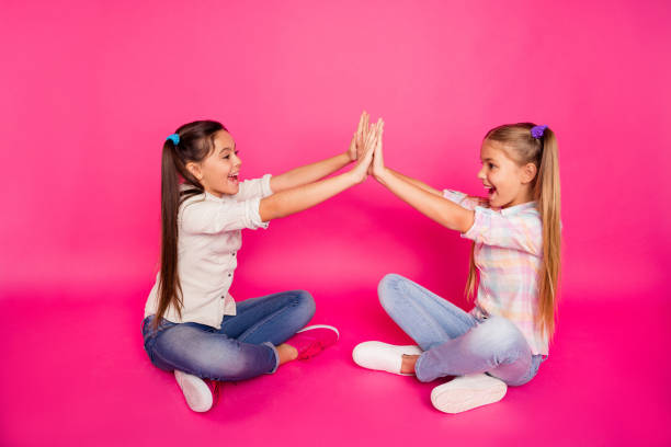 close up side profile photo two little age she her girls hands arms clap best friends sit floor legs crossed wearing casual jeans denim checkered plaid shirts isolated rose vibrant vivid background - pigtails stock photos and pictures