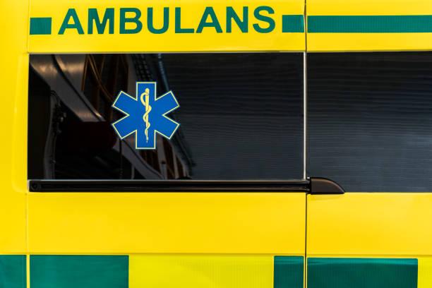 Close up side view of a yellow and green Swedish ambulance vehicle. stock photo