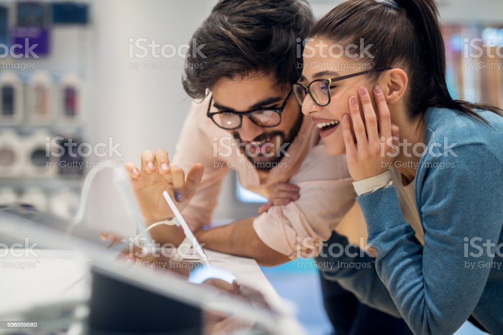 Close up side view of pretty happy excited hipster young love couple testing new smart gadgets in a tech store. stock photo