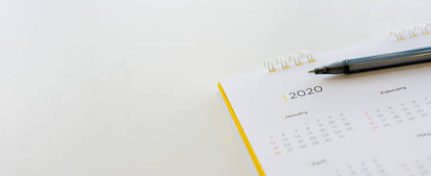 close up side view on  white calendar schedule background with pen to make appointment meeting or manage timetable each day for planning work in new year 2020 resolution concept - calendar imagens e fotografias de stock