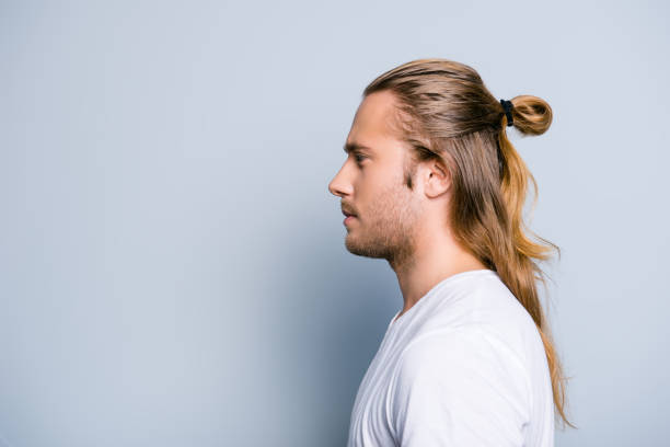 Close up side view photo of serious confident young guy, he has hair bun, isolated on grey background stock photo