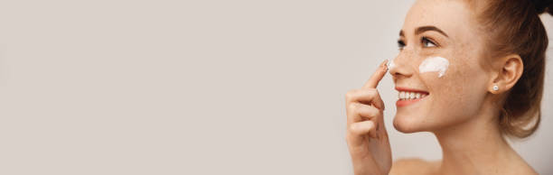 Close up side view portrait of a charming young woman with red hair and freckles applying cream on her face and nose with finger laughing isolated on white wall stock photo