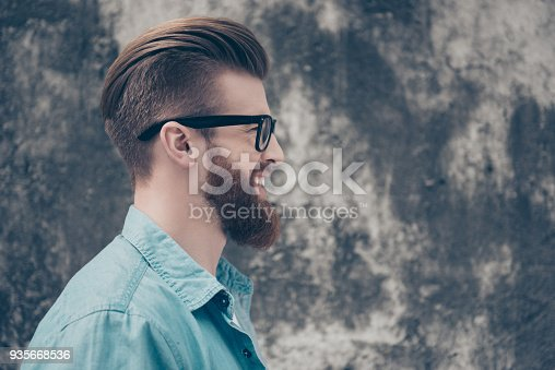 932956896istockphoto Close up side view portrait of happy smiling man in casual jeans clothes and black spectacles standing against concrete wall near the copy space 935668536