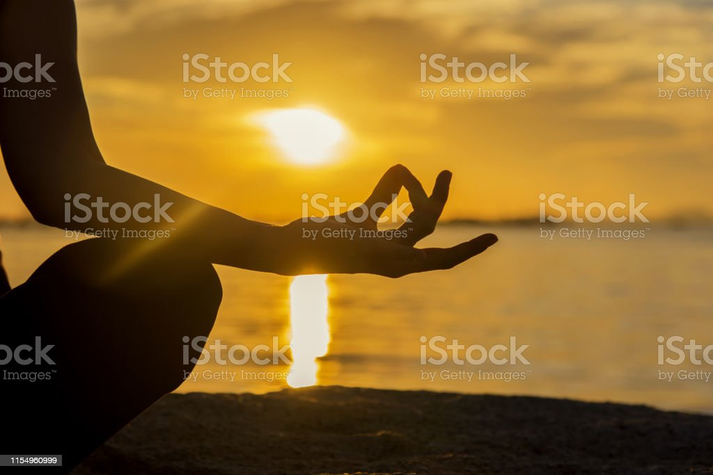 Close up Silhouette hands. Woman do yoga outdoor. Woman exercising...