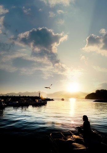 Silhouetted man fishing in Antalya harbor with crowd of silhouetted people over sunset sky and high mountains