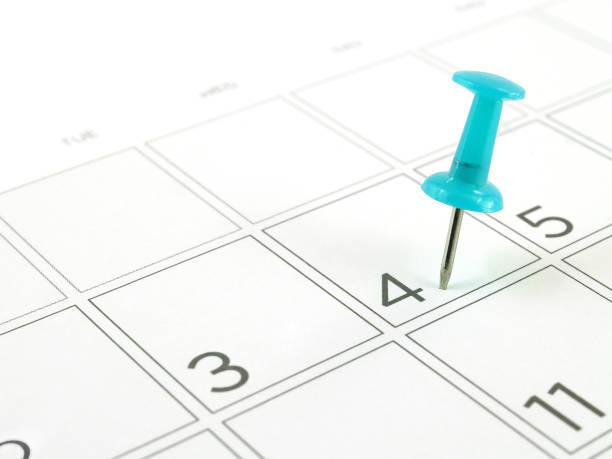 nahaufnahme einzelne blaue kunststoff push-pin-tacking in zeitplan-box vom 4. juli auf white desk kalenderseite - letzter arbeitstag stock-fotos und bilder