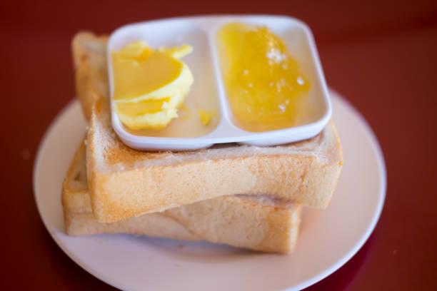 nahaufnahme der scheibe toastbrot mit marmelade und butter - ananas marmelade stock-fotos und bilder