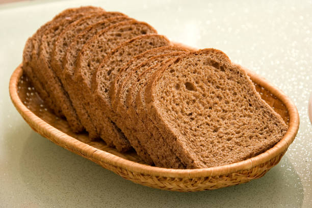 Close up sliced brown bread in wicker bowl on kitchen table stock photo