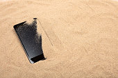 Close up smart phone on sand beach texture background. Copy space of technology and travel nature concept