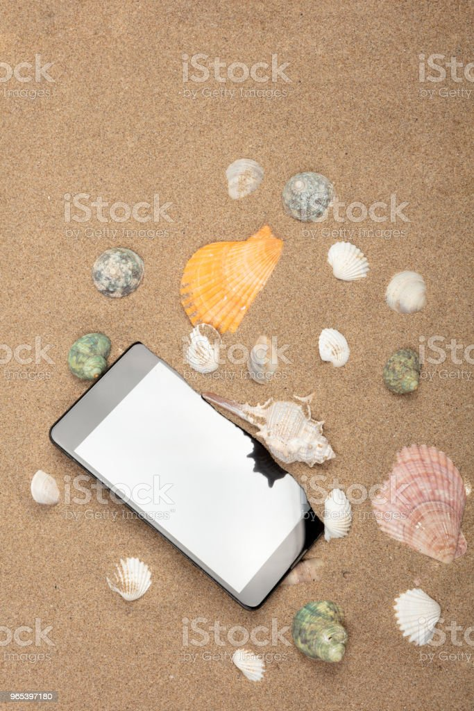 Close up smart phone on sea sand with copy space royalty-free stock photo