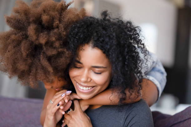 close up smiling african american mother embracing with daughter - um animal imagens e fotografias de stock
