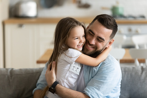 Close up smiling loving young father hugging adorable little daughter, enjoying tender moment, spending weekend together, sitting on cozy couch at home, good family relationship between dad and child