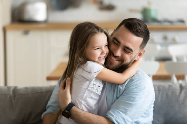 Close up smiling loving young father hugging adorable little daughter stock photo