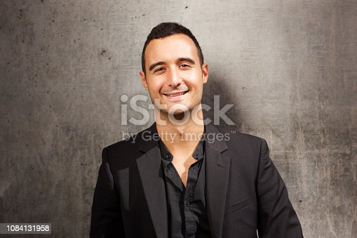 istock Close up smiling man posing against gray wall with black blazer 1084131958