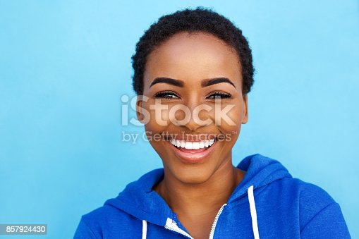 istock Close up smiling young black woman against blue background 857924430