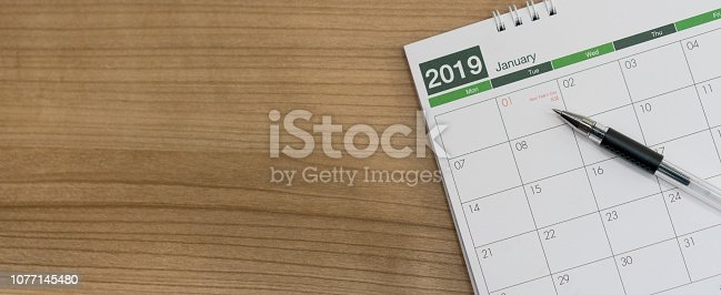 istock close up soft focus on ink pen over calendar 2019 at wood desk background (top view) for make appointment or remember important event on date concept 1077145480