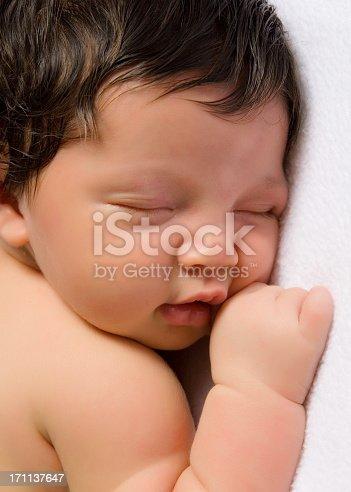 Close up of newborn baby sleeping on soft, white blanket.