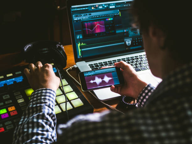 close up sound producer's hand holding phone and using app to create music in sound recording studio close up sound producer's hand holding phone and using app to create music in sound recording studio synthesizer stock pictures, royalty-free photos & images