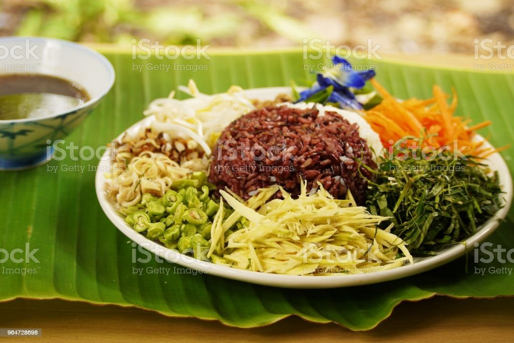 Close up Spicy Rice Salad with Vegetable and Budu Fish sauce southern style on banana leaf  prepare for serving , Thai traditional  healthy home made food  image for background. royalty-free stock photo
