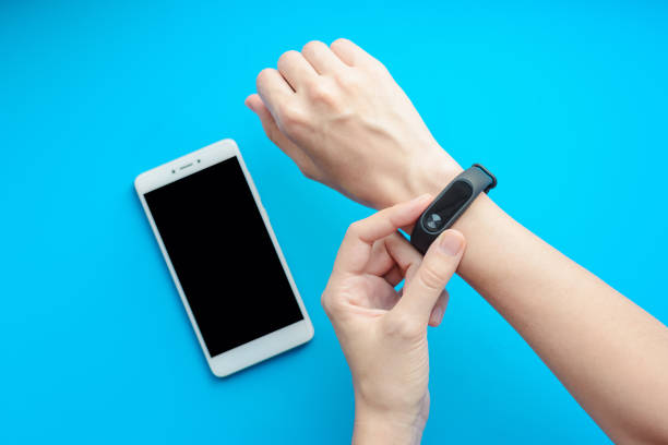 close up sport girl using fitness tracker on hand and smartphone on blue background close up sport girl using fitness tracker on hand and smartphone on blue background close up fitness tracker stock pictures, royalty-free photos & images