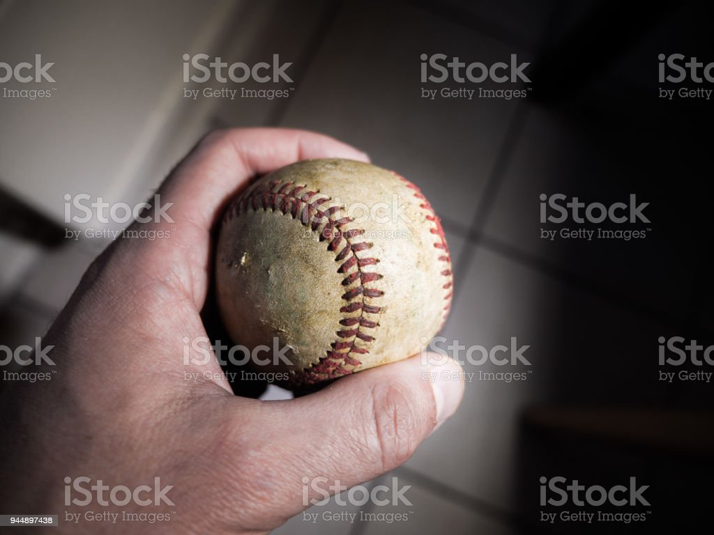 Close up sports background image of a male hand holding an old used weathered leather baseball between his thumb and fore finger showing intricate detailing and red laces. stock photo