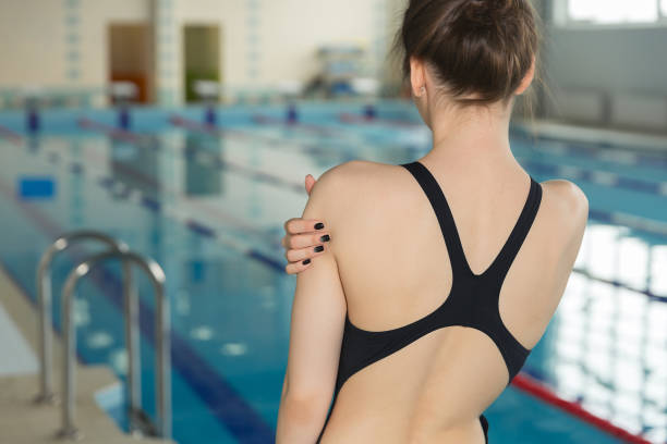 Sportler mit Schmerzen in der Schulter vor dem Moment stehen in der Nähe von Pool schwimmen hautnah. – Foto