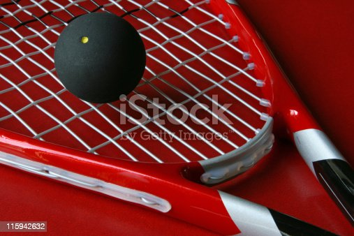 Close-up of a squash racket and a ball on a red background.