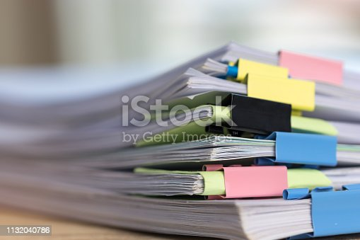 Close up stack of paperwork. Pile of unfinished homework assignment stacked in archive with colorful binder paper clips on table waiting to be managed and inspected. Education and business concept.