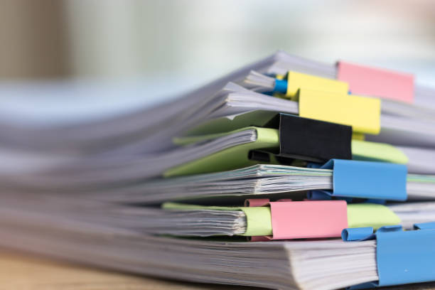 close up stack of paperwork. pile of unfinished homework assignment stacked in archive with colorful binder paper clips on table waiting to be managed and inspected. education and business concept. - rapporto foto e immagini stock