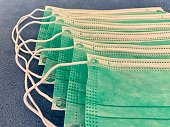 Close up of stack of green surgical face protection masks on blue fabric