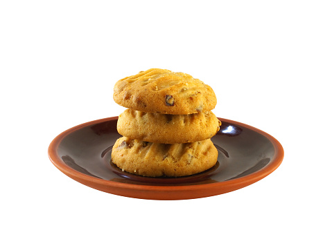close up stack of three biscuit cookies on brown ceramic baked clay dish isolated on white background