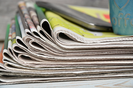 Close up  stacked newspapers with smartphone on wooden table background