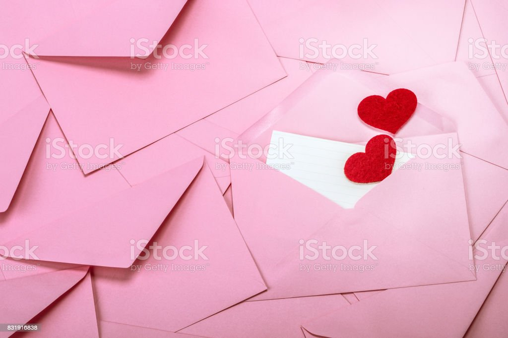 close up Stacking of pink envelopes and mail letter paper and red herat , the  romance  love letter concept for holiday valentines day greeting card concept close up Stacking of pink envelopes and mail letter paper and red herat , romance  love letter concept for holiday valentines day greeting card concept Blank Stock Photo