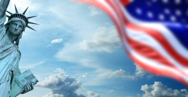 Close up Statue of Liberty and American flag over stormy sky stock photo