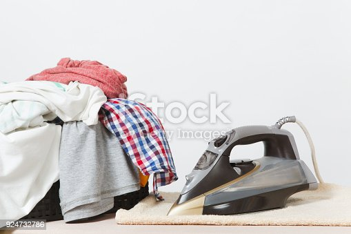 932671892 istock photo Close up steam iron, ironing colorful clothes, washed laundry, family clothing on ironing board isolated on white background. Housekeeping concept. Copy space for advertisement. With place for text. 924732786