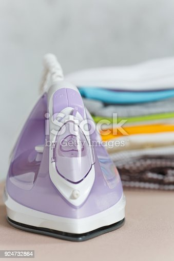932671892 istock photo Close up steam iron, ironing colorful clothes, washed laundry, family clothing on ironing board isolated on white background. Housekeeping concept. Copy space for advertisement. With place for text. 924732864