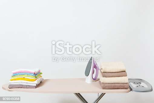 932671892 istock photo Close up steam iron, ironing colorful clothes, washed laundry, family clothing on ironing board isolated on white background. Housekeeping concept. Copy space for advertisement. With place for text. 929545058