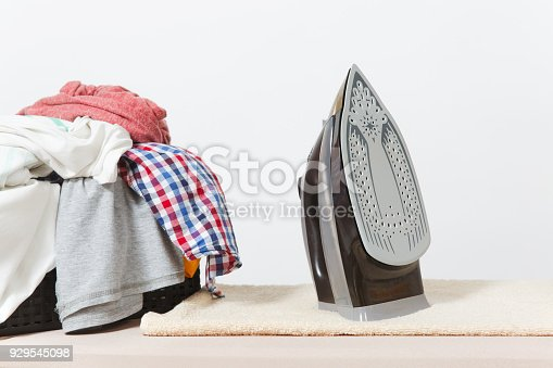 932671892 istock photo Close up steam iron, ironing colorful clothes, washed laundry, family clothing on ironing board isolated on white background. Housekeeping concept. Copy space for advertisement. With place for text. 929545098