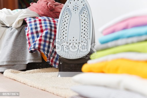 932671892 istock photo Close up steam iron, ironing colorful clothes, washed laundry, family clothing on ironing board isolated on white background. Housekeeping concept. Copy space for advertisement. With place for text. 932673974