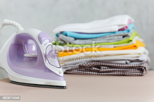 932671892 istock photo Close up steam iron, ironing colorful clothes, washed laundry, family clothing on ironing board isolated on white background. Housekeeping concept. Copy space for advertisement. With place for text. 932674046