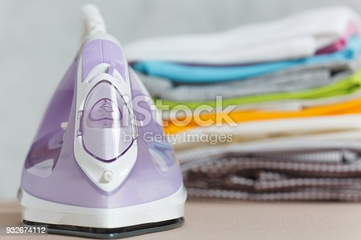 932671892 istock photo Close up steam iron, ironing colorful clothes, washed laundry, family clothing on ironing board isolated on white background. Housekeeping concept. Copy space for advertisement. With place for text. 932674112