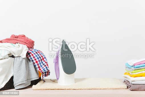932671892 istock photo Close up steam iron, ironing colorful clothes, washed laundry, family clothing on ironing board isolated on white background. Housekeeping concept. Copy space for advertisement. With place for text. 936818360