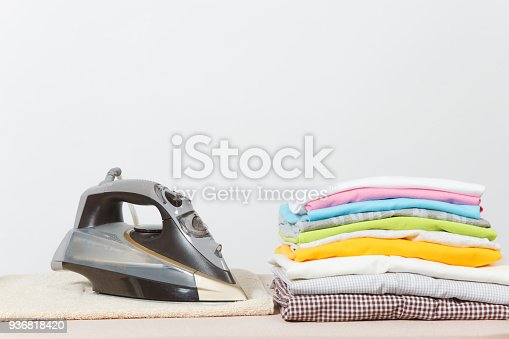 932671892 istock photo Close up steam iron, ironing colorful clothes, washed laundry, family clothing on ironing board isolated on white background. Housekeeping concept. Copy space for advertisement. With place for text. 936818420