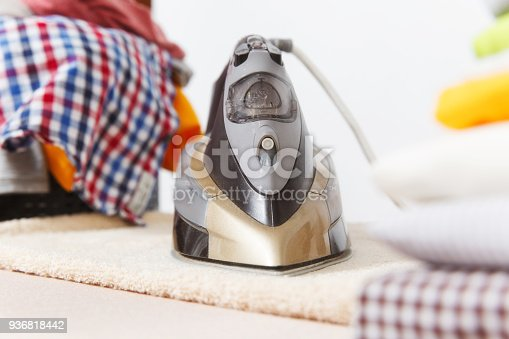 932671892 istock photo Close up steam iron, ironing colorful clothes, washed laundry, family clothing on ironing board isolated on white background. Housekeeping concept. Copy space for advertisement. With place for text. 936818442