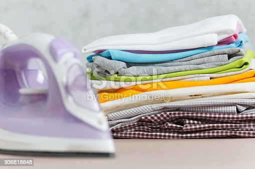 932671892 istock photo Close up steam iron, ironing colorful clothes, washed laundry, family clothing on ironing board isolated on white background. Housekeeping concept. Copy space for advertisement. With place for text. 936818648