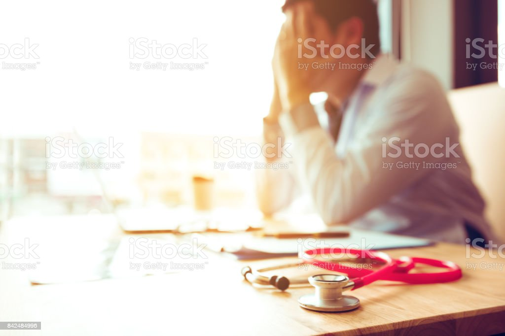 Close up stethoscope and asian doctor sitting with laptop with stress headache. stock photo