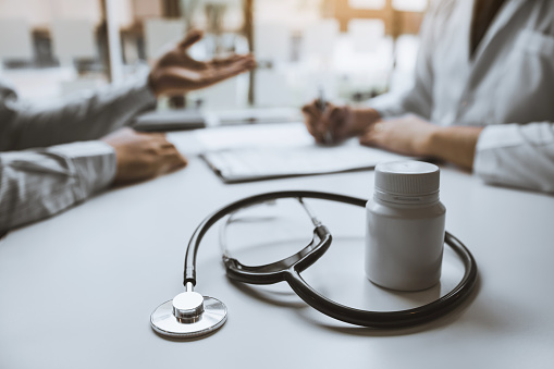873418972 istock photo Close up stethoscope and doctor talking the patient at clinic while using the tablet explaining the patient condition and the treatment result. 1188795377