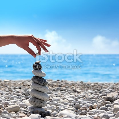istock Close up stone pile and female fingers holding little stone over clear sky 998369858