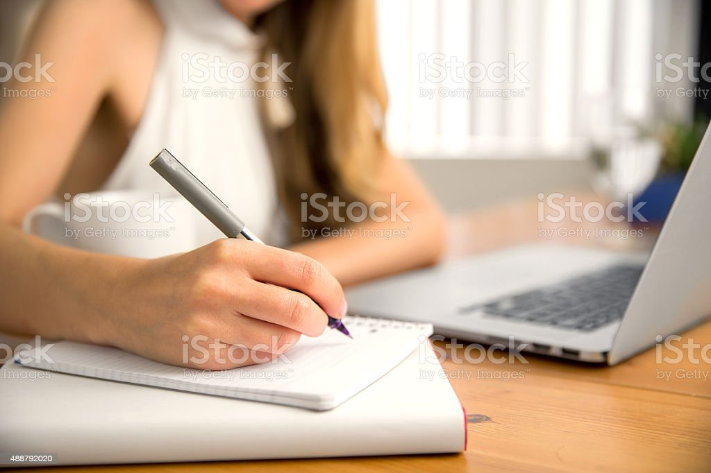 Close up student business hand laptop computer notes studying home